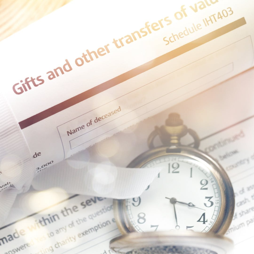 Close up of inheritance tax form and a pocket watch