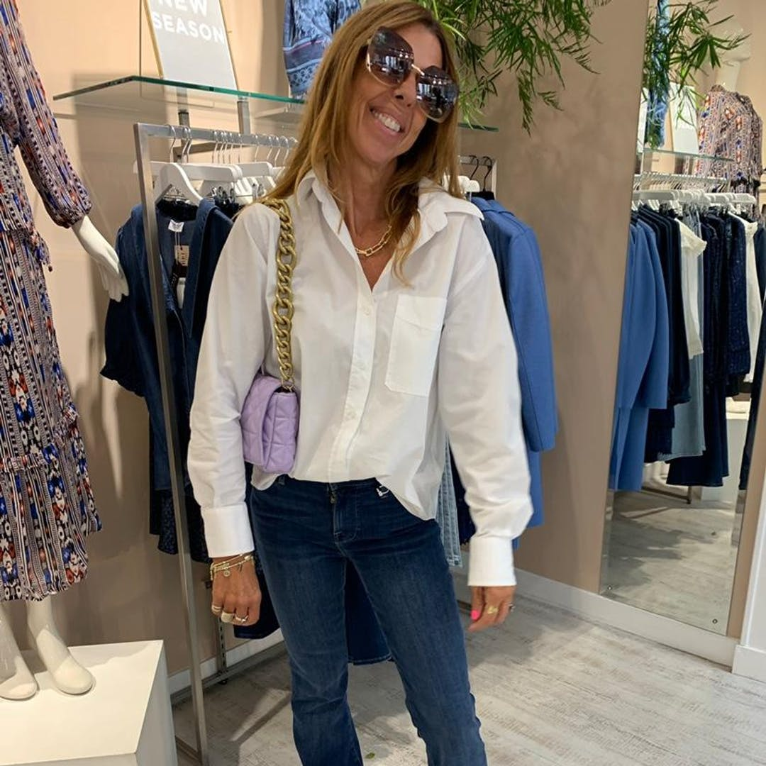 Lady in shop wearing jeans white shirt sunglasses long hair