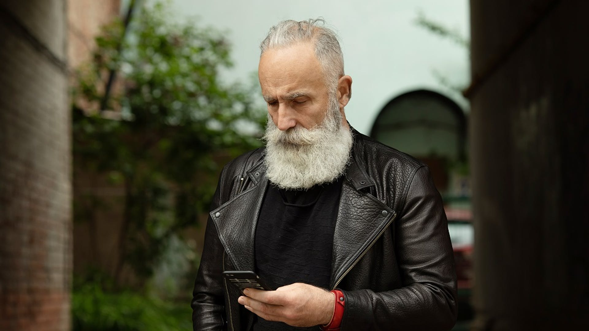 mature man in leather jacket looking at mobile phone