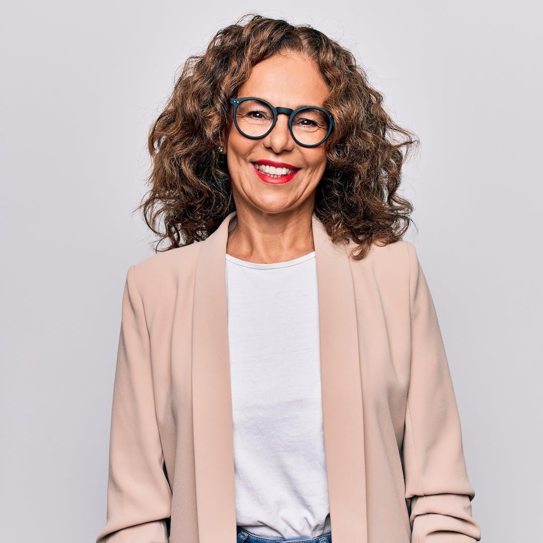 mature woman wearing glasses smiling at camera