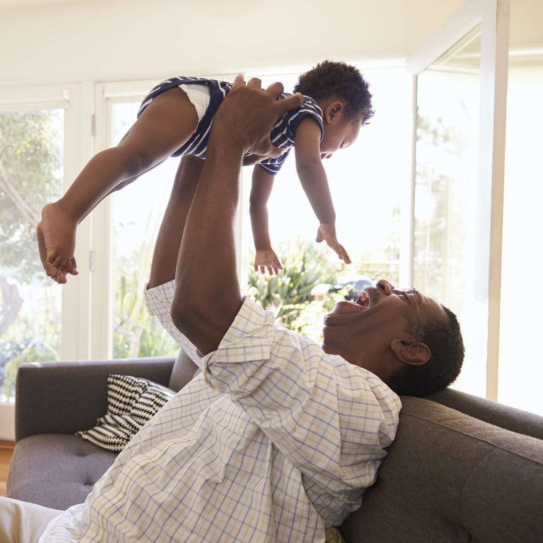 smiling father playing with infant child in the air