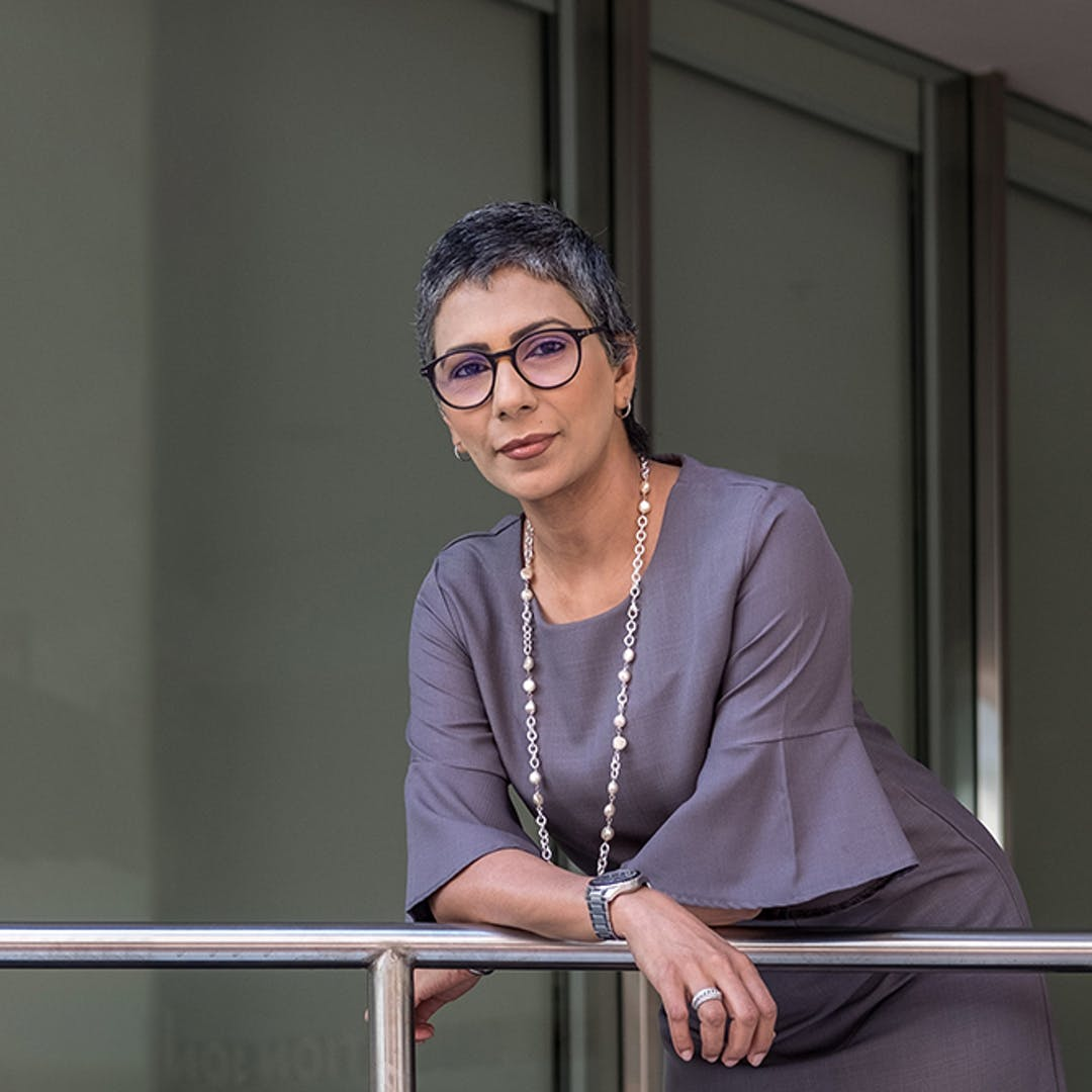 Woman in 50s wearing glasses purple top necklace leaning on balcony